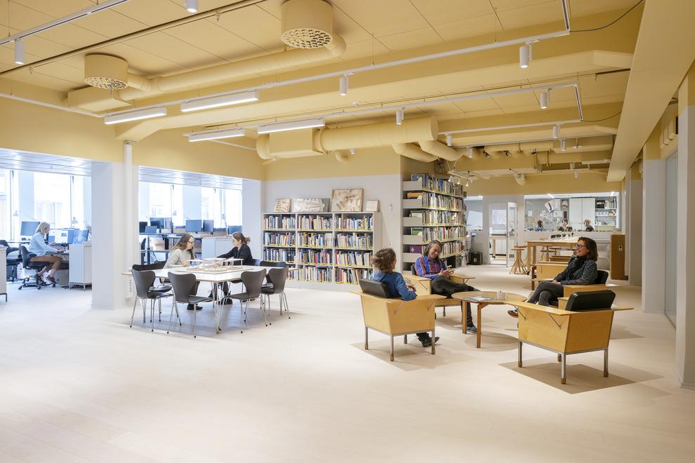 Nyréns Arkitektkontors arbetsplats på Magnus Ladulåsgatan 63. Medarbetare sitter i företagets biblioteket. I bakgrunden synd personer som jobbar vid dator eller har möte.