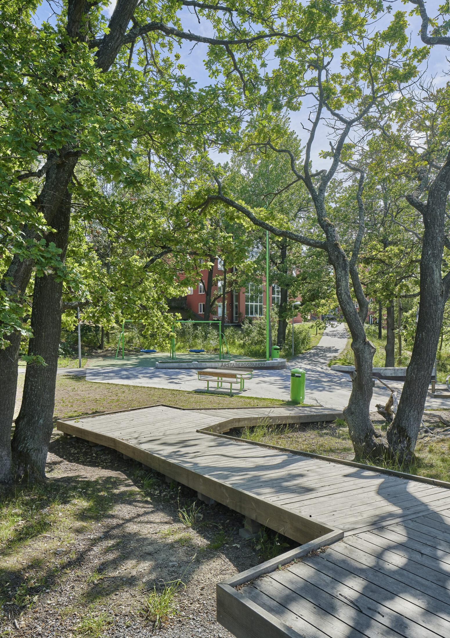 Gångvägar i trä bland träden i Årstabergsparken.