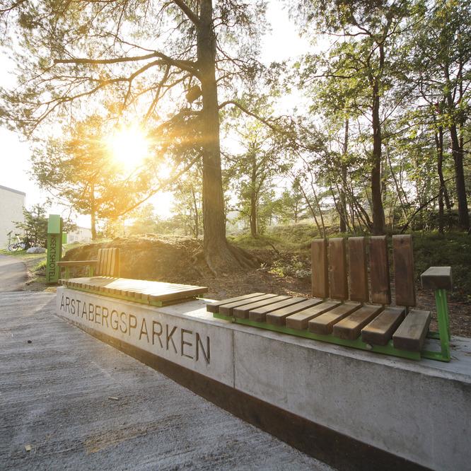 Längs en betongmur finns sittplatser. Parkens namn är skrivet på muren.