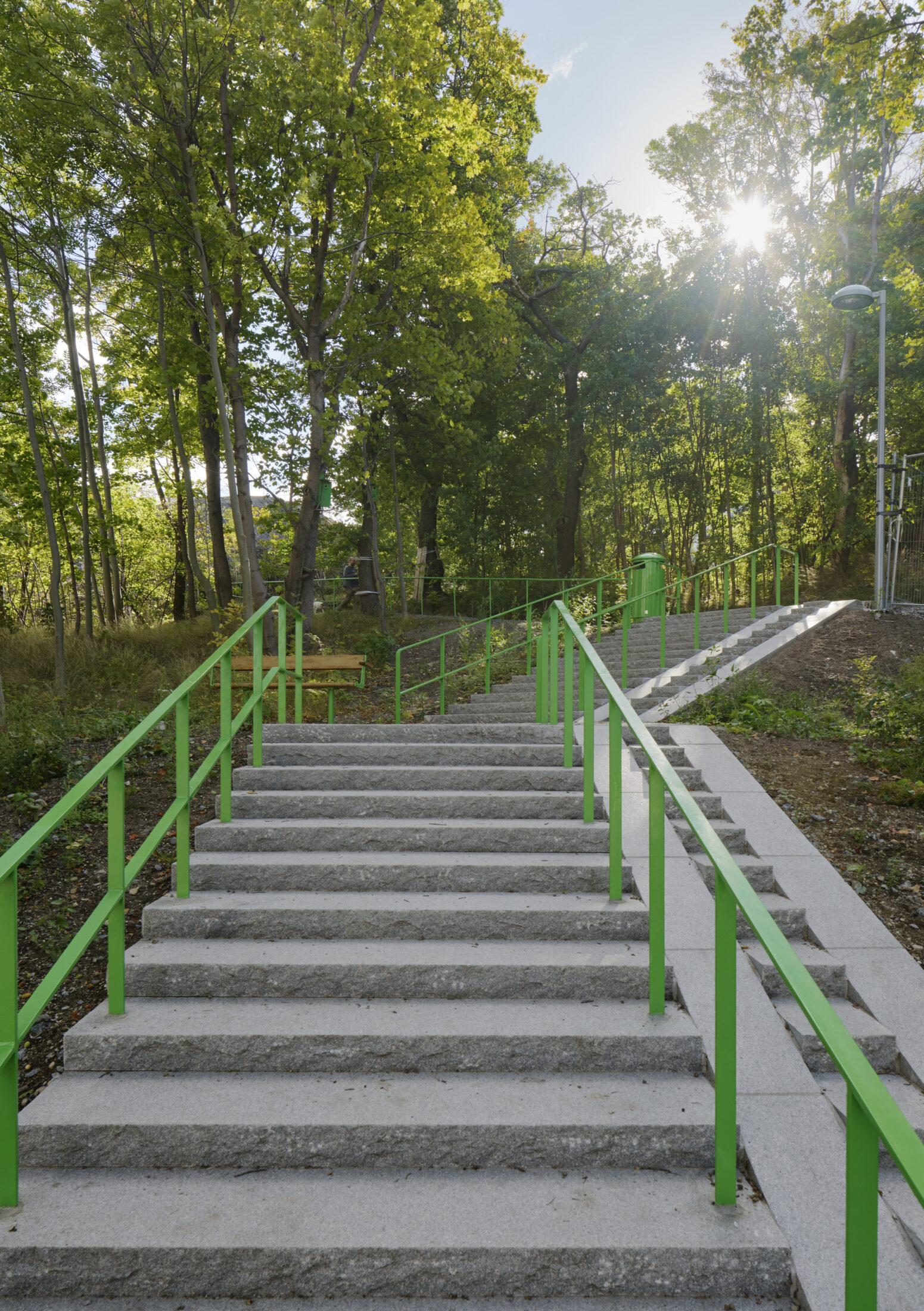 Stentrappa leder vägen upp i Årstabergsparken. Gröna trappräcken på var sida.