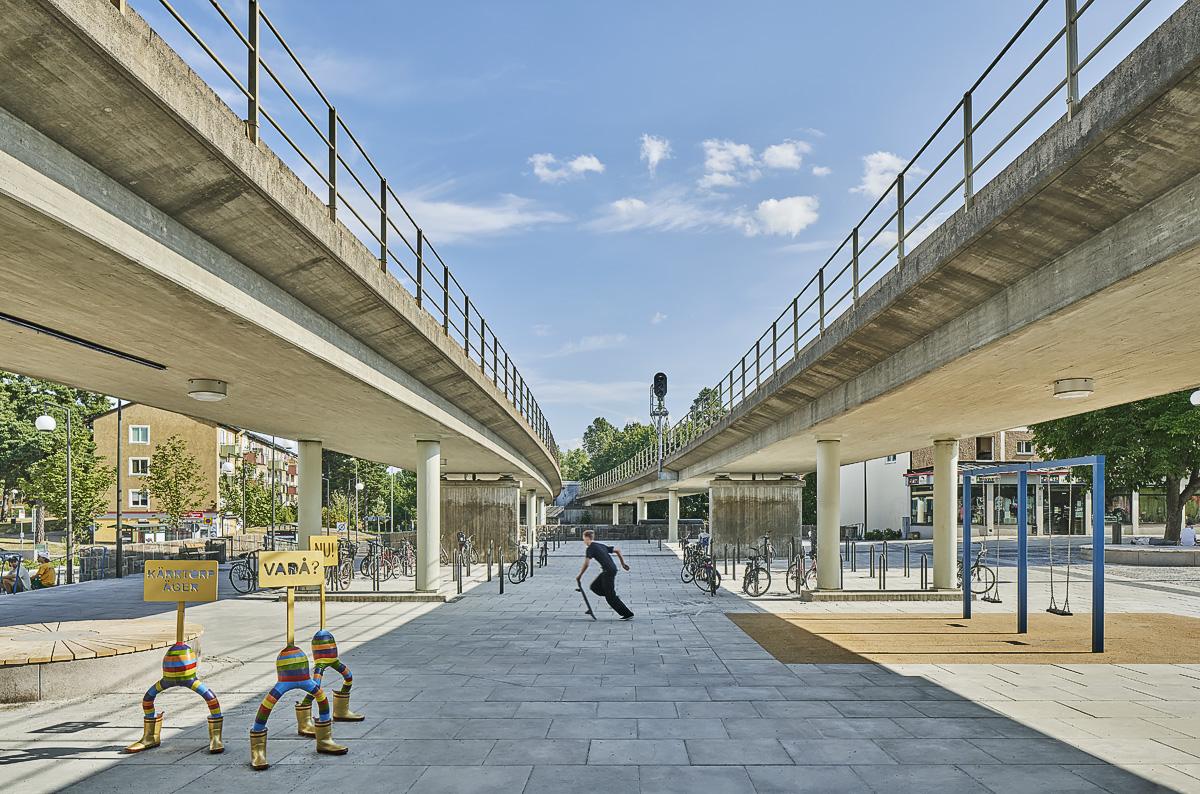 Kärrtorp Centrum, under bron skulpturer och gungor foto